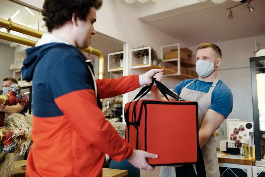 man-in-a-face-mask-handing-over-a-thermal-bag-to-another-man-4393668